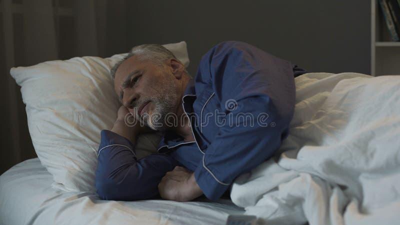 在床上和遭受失眠、消沉和健康的灰发的人 库存照片