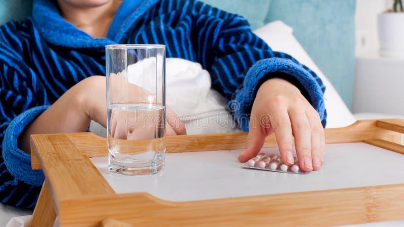在床上和采取从盘子的病的妇女的特写镜头图象药片 库存照片