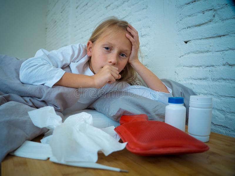 在床上咳嗽感觉的女孩说谎的病残病态与有的发高烧冷的流感 库存图片
