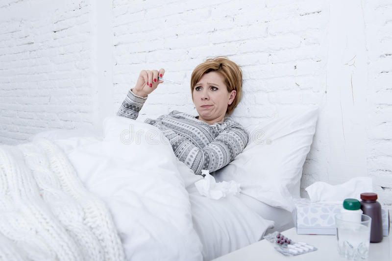 在床上检查温度的病的妇女与温度计狂热微弱的痛苦冷的冬天流感病毒 库存照片