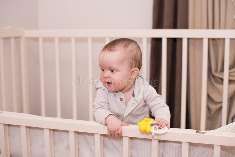 在床上玩玩具的可爱婴儿 新生的孩子,小女孩玩,抓,爬 免版税库存照片