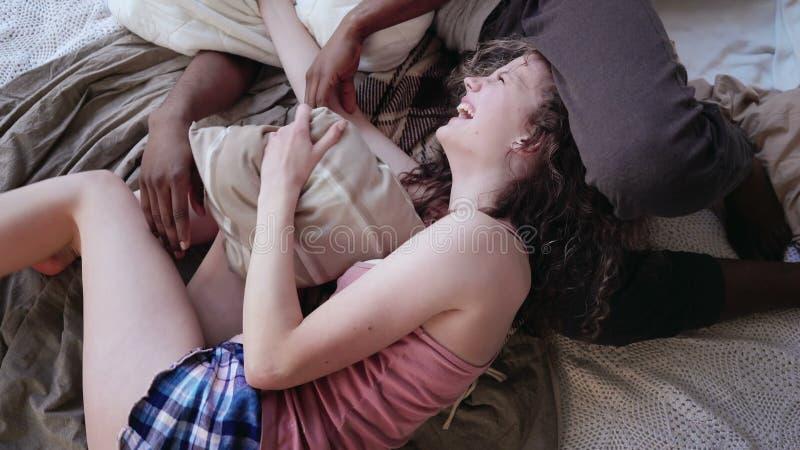 在床上的不同种族的爱恋的夫妇,由枕头的战斗 睡衣的在家度过余暇的妇女和人 库存图片