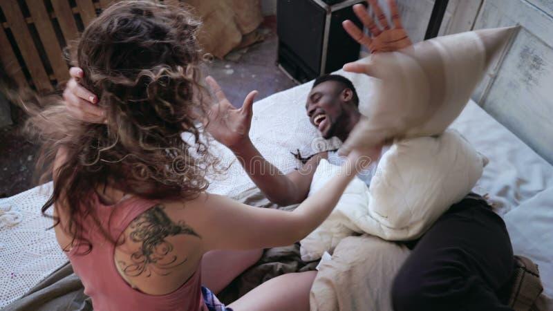 在床上的不同种族的爱恋的夫妇,由枕头的战斗 睡衣的在家度过余暇的妇女和人 图库摄影