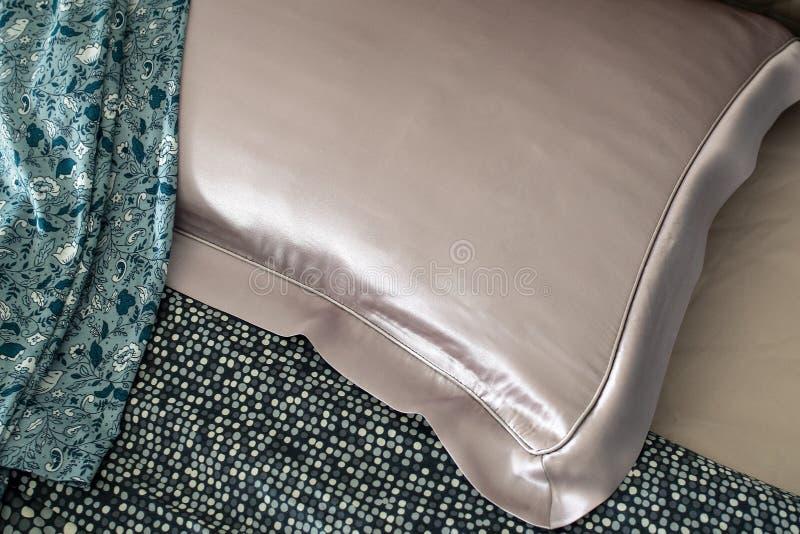 在床上的丝绸枕头 免版税库存图片