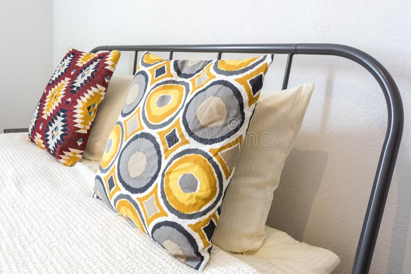 在床上的五颜六色的枕头在现代卧室的内部顶楼平的公寓的在淡色样式 库存图片