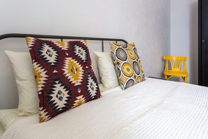 在床上的五颜六色的枕头在现代卧室的内部顶楼平的公寓的在淡色样式 库存照片