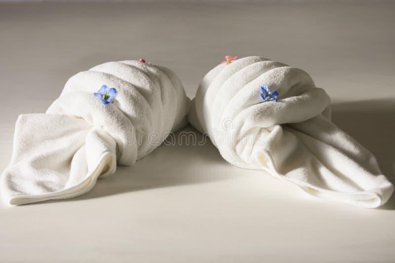 在床上的创造性的毛巾在旅馆,毛巾集合为用途做准备在私有屋子、设备在租屋子里或旅馆里 免版税库存照片