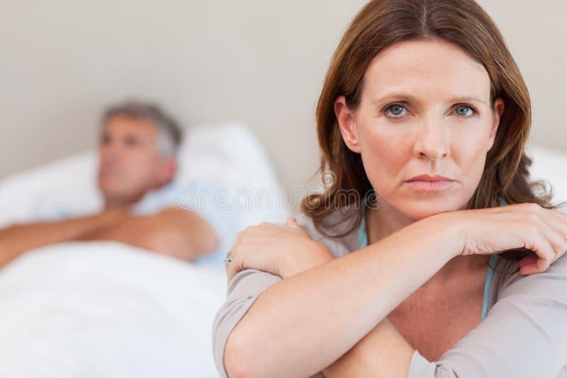 在床上的哀伤的妇女与丈夫在背景中 免版税库存照片