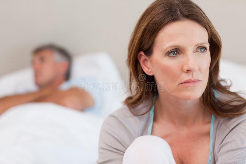 在床上的哀伤的妇女与她的丈夫在背景中 免版税库存图片