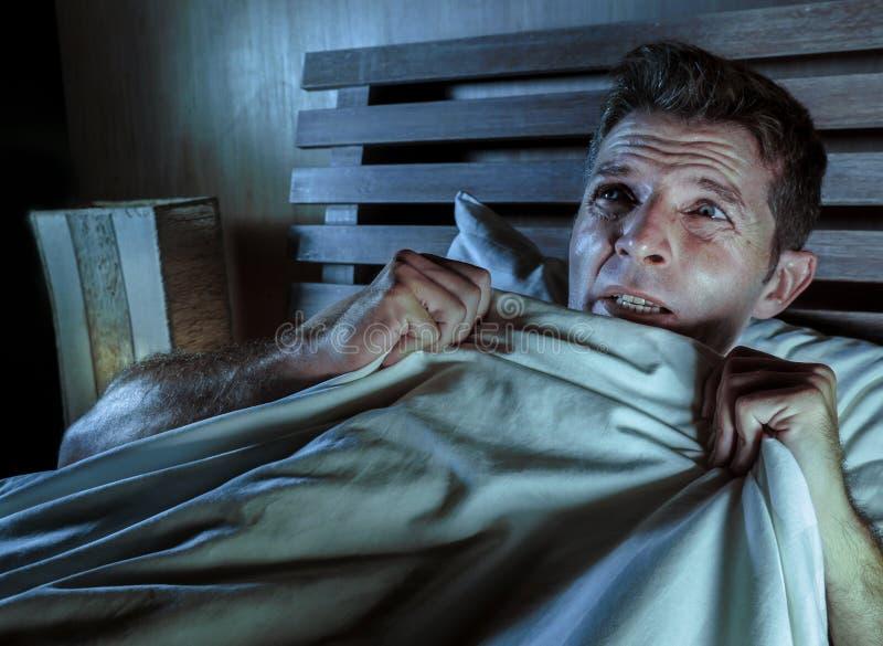 在床上的失眠的年轻人注重了并且惊吓了遭受的恶梦和恐怖坏梦想劫掠的鸭绒垫子害怕的和parano 免版税库存照片