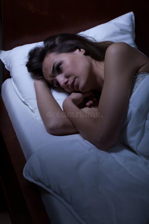 在床上的妇女醒 免版税库存照片