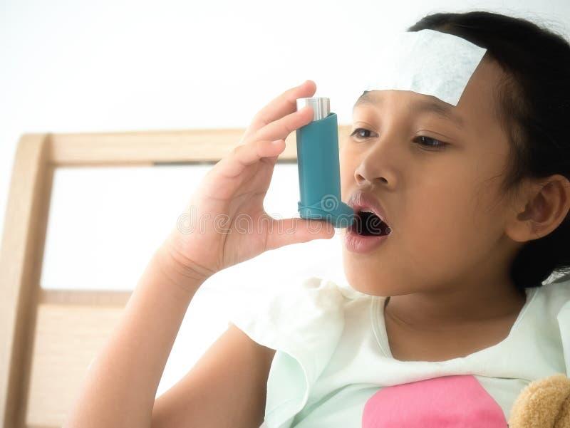 在床上的小女孩使用安心哮喘的a蓝色哮喘吸入器 免版税图库摄影
