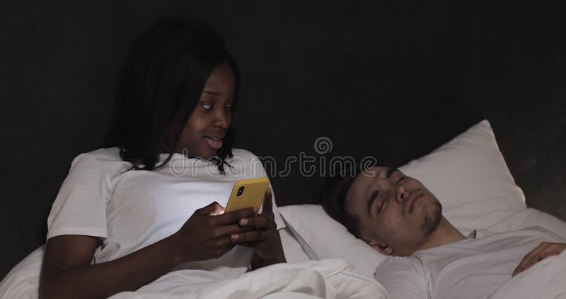 在床上的已婚不同种族的夫妇在晚上 使用智能手机的妇女发短信与恋人,而他的丈夫是 库存照片