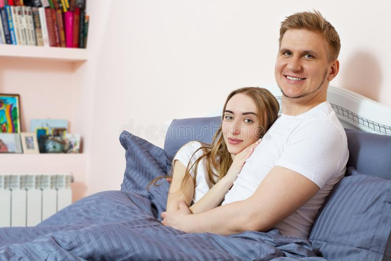 在床上的年轻愉快的夫妇在早晨 免版税图库摄影