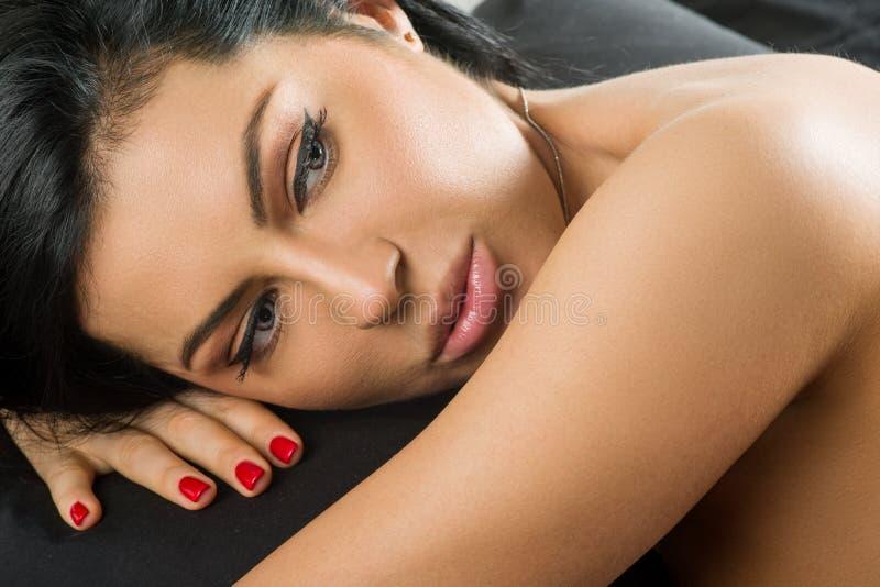 在床上的年轻深色的妇女,背景黑板料 库存照片