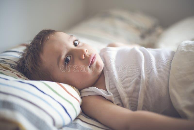 在床上的年轻男孩 免版税库存照片