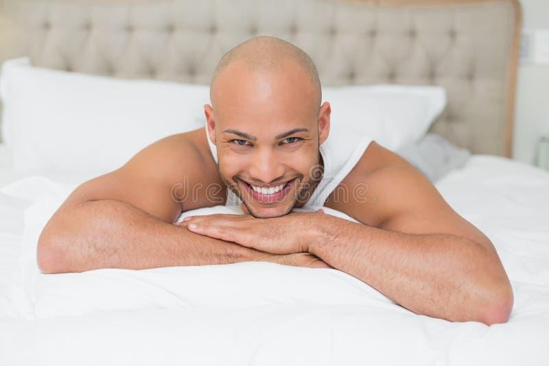 在床上的微笑的偶然秃头年轻人 免版税库存图片