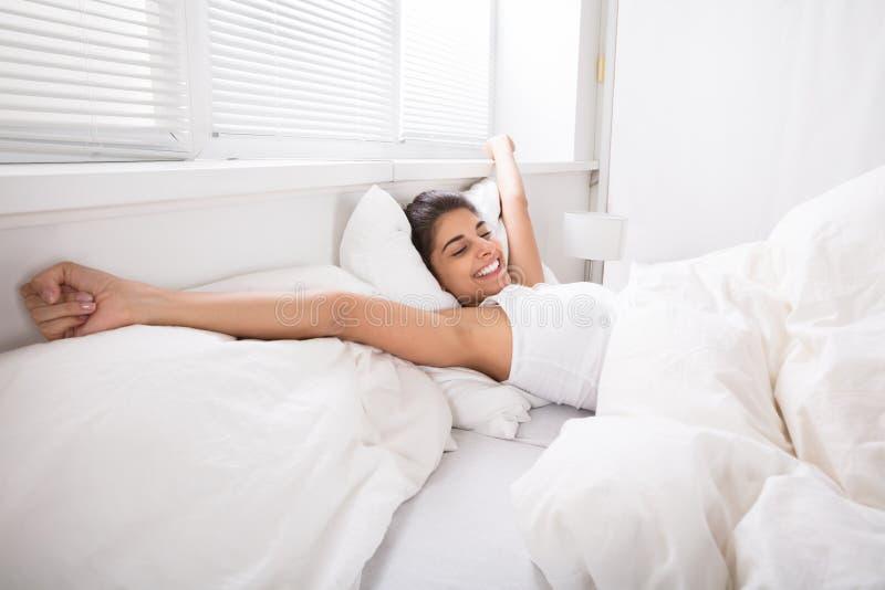在床上的微笑的妇女醒 库存图片