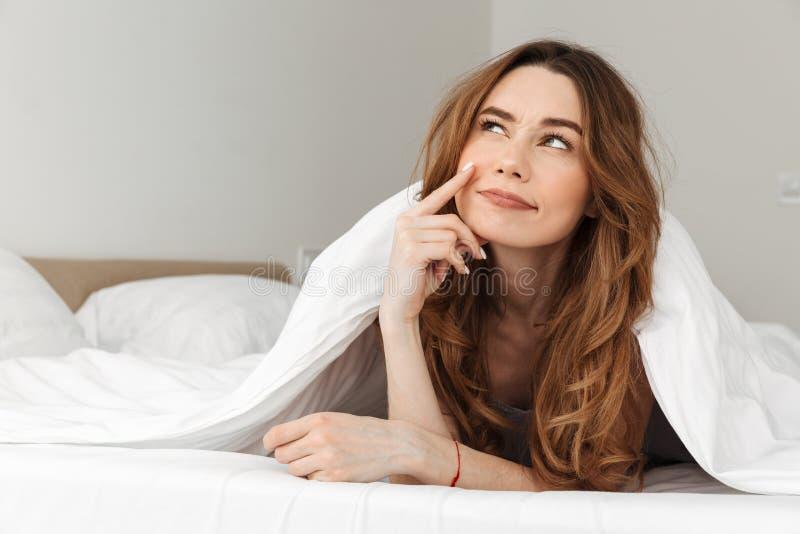 在床上的微笑的妇女20s画象在白色毯子下我 免版税库存图片
