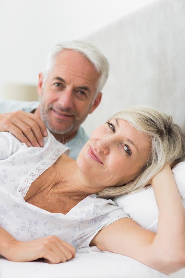 在床上的微笑的成熟夫妇特写镜头画象  免版税库存照片