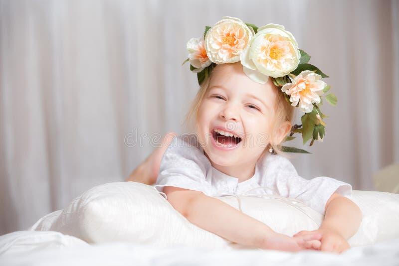 在床上的愉快的小女孩 免版税图库摄影