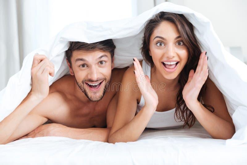 在床上的愉快的微笑的夫妇盖用毯子 库存照片