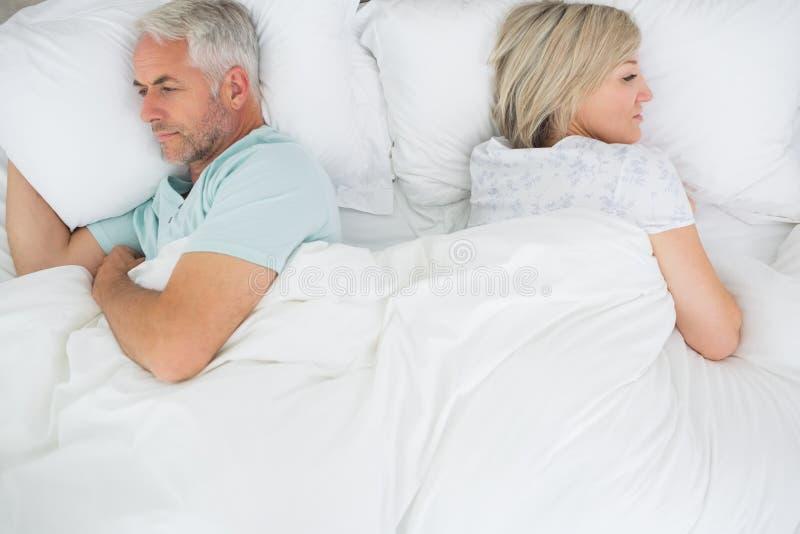 在床上的成熟夫妇 免版税图库摄影