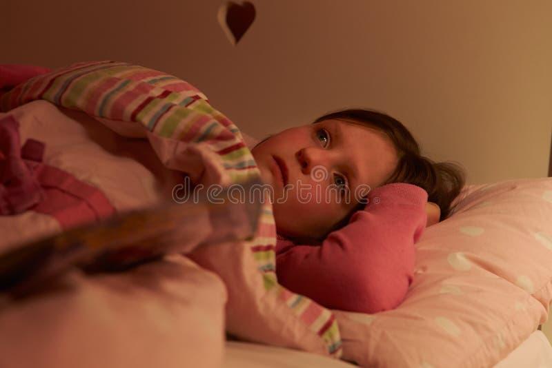 在床上的担心的女孩醒在晚上 免版税库存图片