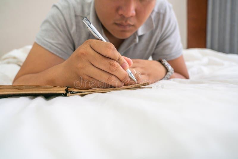 在床上的接近的人谎言和采取笔记 免版税库存照片