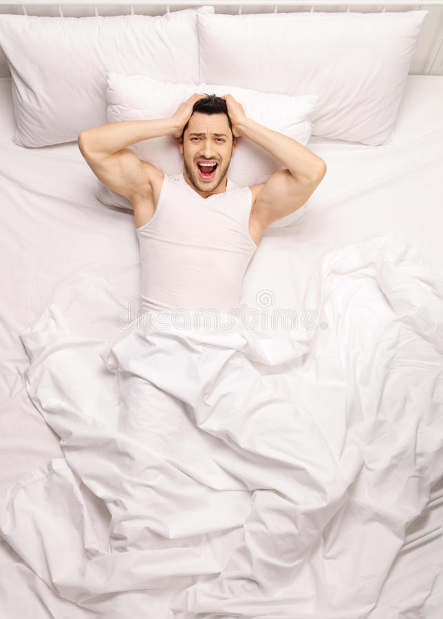在床上的沮丧的人 免版税库存图片