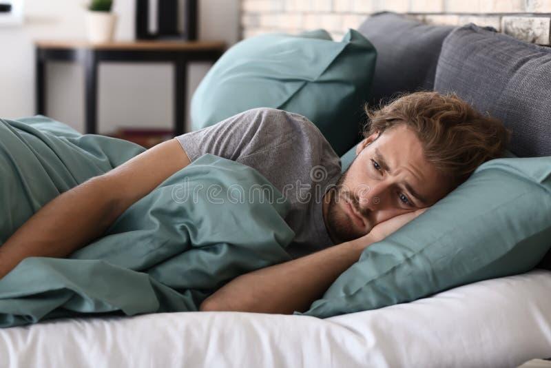 在床上的沮丧的年轻人 免版税库存图片