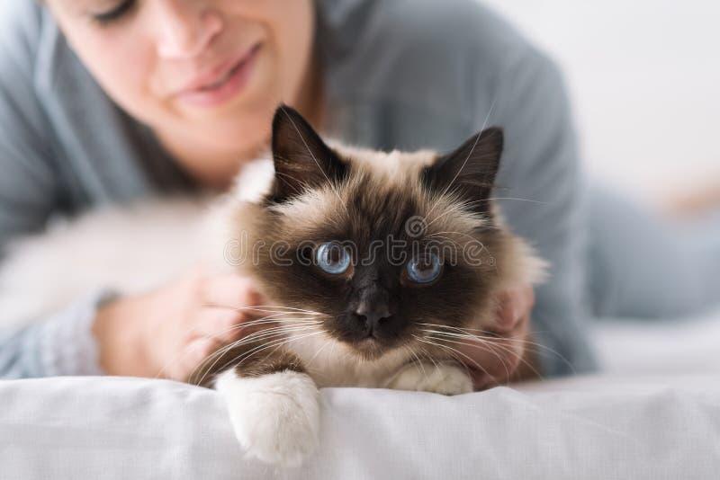 在床上的爱拥抱猫 库存照片