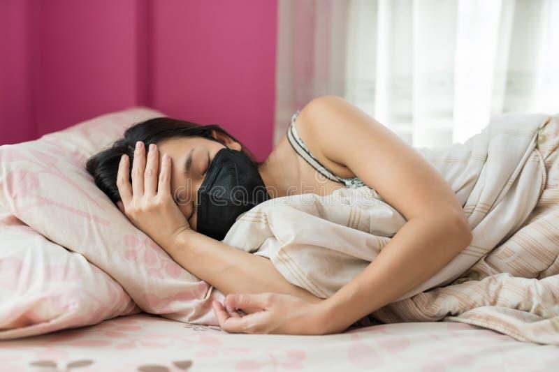 在床上的病态的亚洲女孩头疼 免版税库存照片