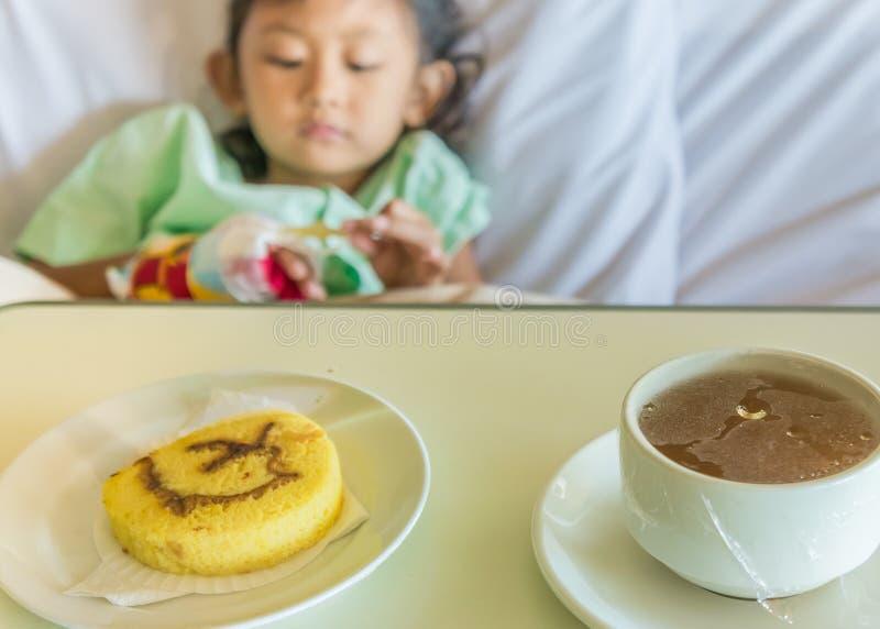 在床上的病的亚裔儿童医院患者与早餐饭食菜单 图库摄影