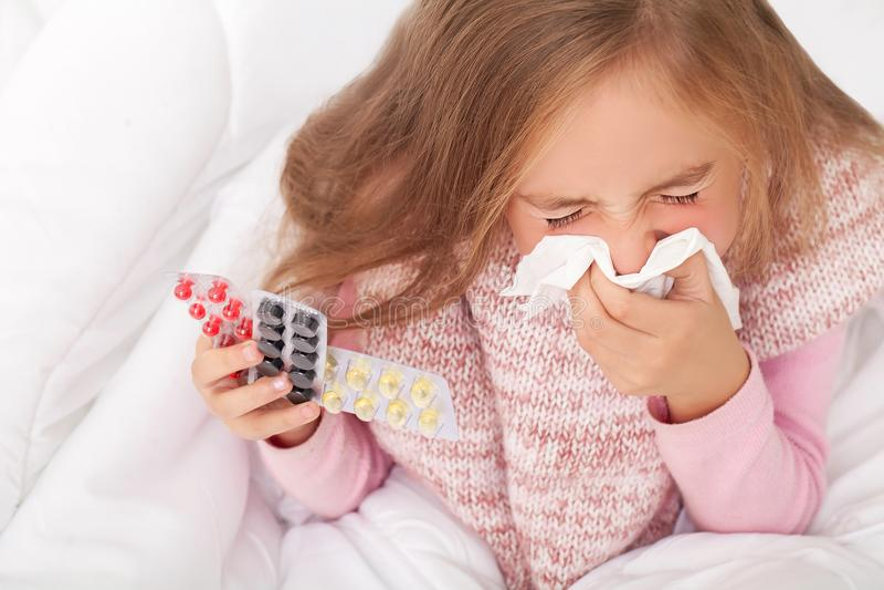 在床上的病的女孩打喷嚏在手帕的在卧室 免版税库存照片