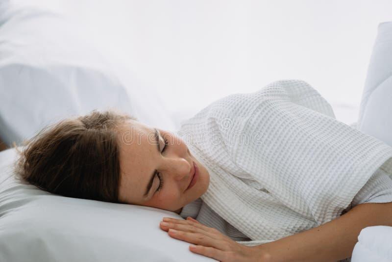 在床上的白种人妇女睡眠在白色卧室 免版税图库摄影