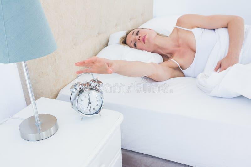 在床上的白肤金发的妇女到达为闹钟 免版税库存图片