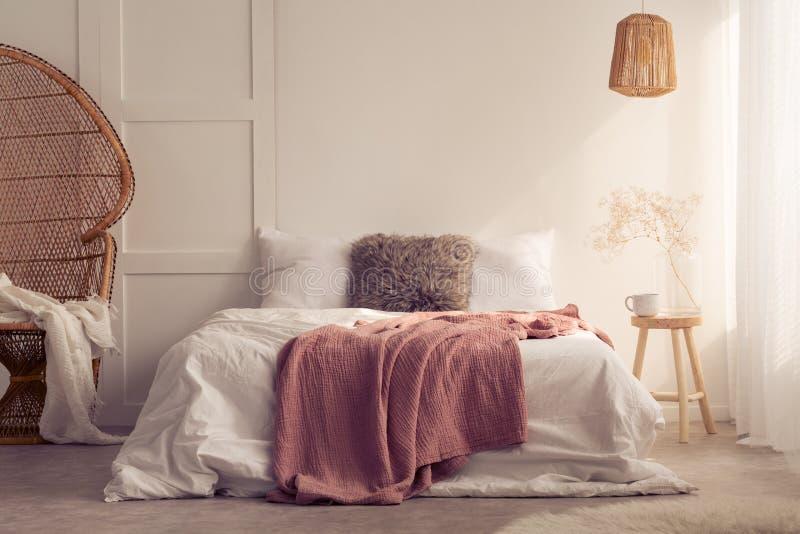 在床上的红色毯子与在白色卧室内部的坐垫与灯和藤条椅子 免版税图库摄影