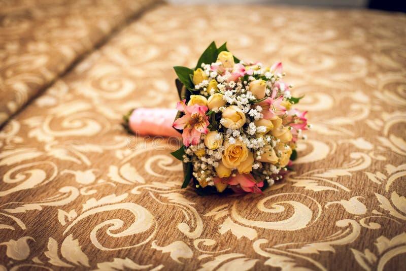 在床上的美丽的新娘的花束 婚姻的花 新婚之夜 免版税图库摄影