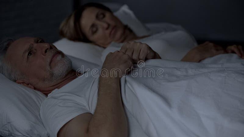 在床上的老人有坚硬想法,不忠实的联系,麻烦 免版税库存图片