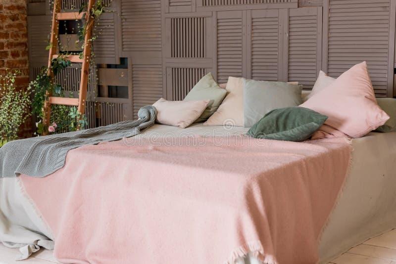 在床上的轻的米黄桃红色毯子与绿色薄荷的枕头 时髦的舒适斯堪的纳维亚卧室内部:床,木梯子 库存图片