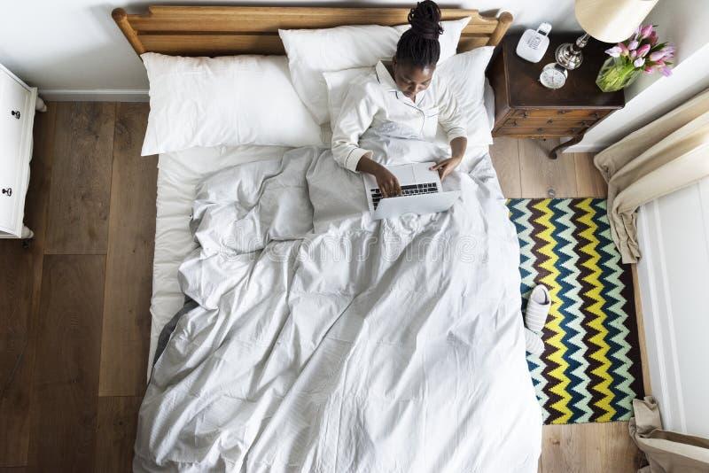 在床上的非裔美国人的妇女使用膝上型计算机 免版税图库摄影