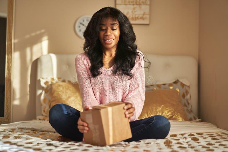 在床上的非裔美国人的妇女开头箱子 免版税库存照片