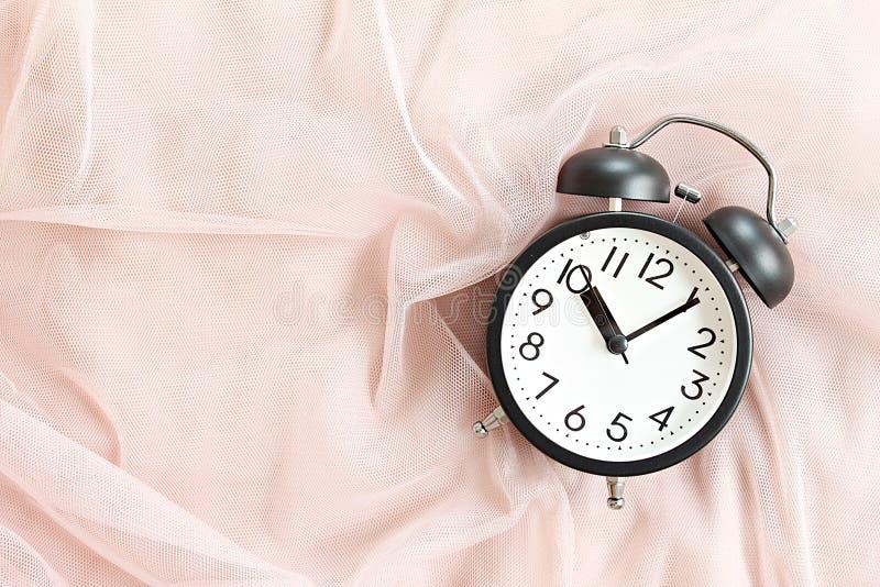 在床上的黑减速火箭的闹钟在早晨、顶视图或者平的位置与拷贝空间准备好加起来或嘲笑 免版税库存照片