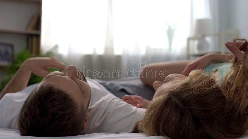 在床上,笑和享受时间,嫩联系的愉快的年轻夫妇 免版税图库摄影