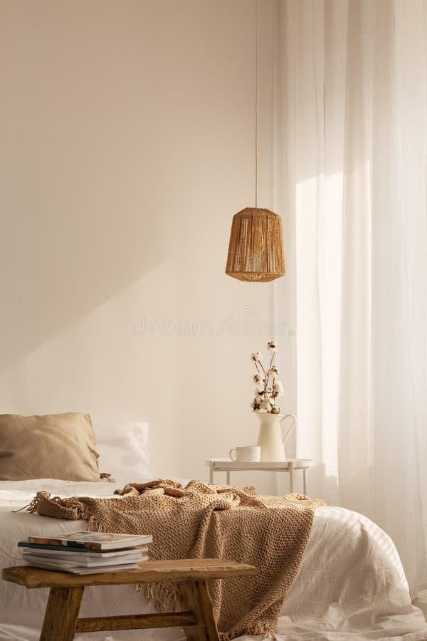 在床前面的板凳与在自然卧室内部的亚麻制毯子与灯 免版税库存图片
