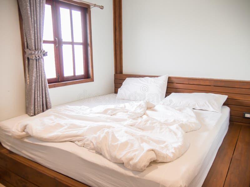 在床和一条杂乱毯子上的白色枕头在卧室 免版税库存图片