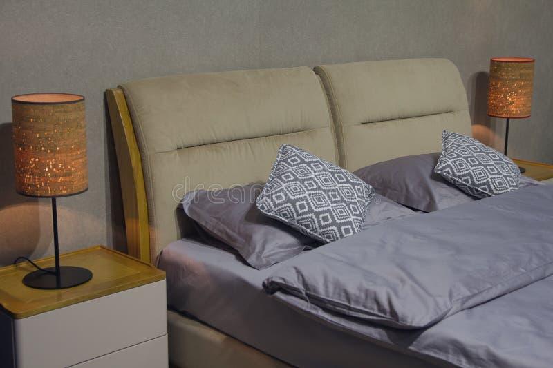 在床和一盏灯上的枕头在一个现代样式 免版税库存照片