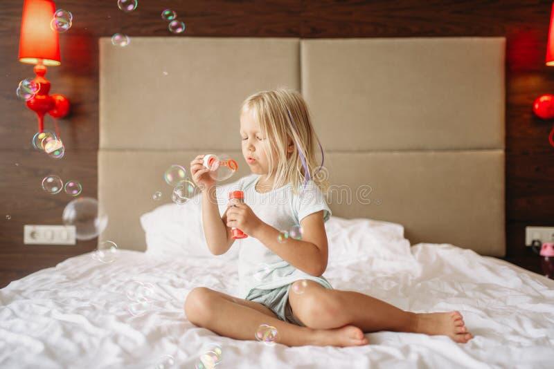 在床和吹的泡影上的女孩 免版税库存照片