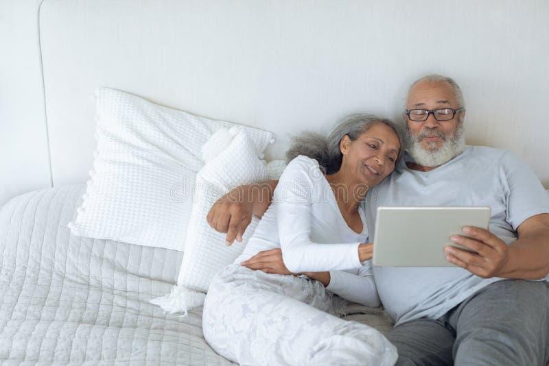 在床和观看的数字片剂上的夫妇 库存图片